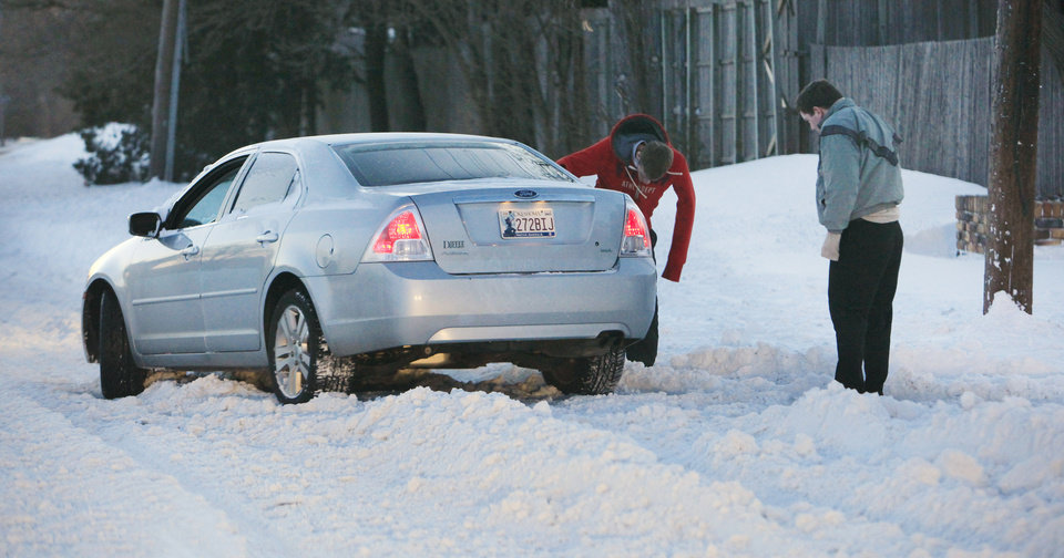 Photo - Motorists try to free a car stuck in the snow on NW 63 Street  just before sunrise in Oklahoma City Wednesday, Feb. 2, 2011. Photo by Paul B. Southerland, The Oklahoman