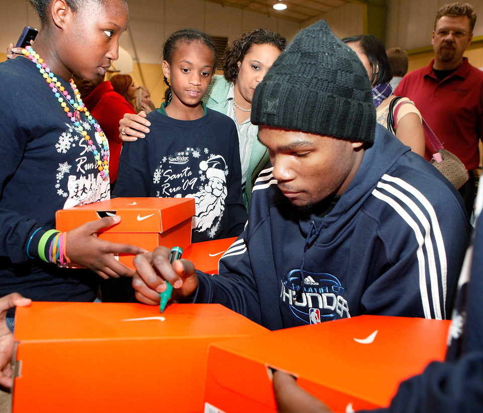 SHOE DONATION / DONATE: Player Kevin Durant autographs shoe boxes for students after they received new shoes. Players from the Oklahoma City Thunder NBA basketball team were joined by mascot, Rumble, and Thunder Girls in assisting children at Dunbar Elementary School in trying on their new Nike athletic shoes donated by SandRidge employees Thursday, Dec. 17, 2009. Each player told the students their favorite holiday song. Nick Collison: