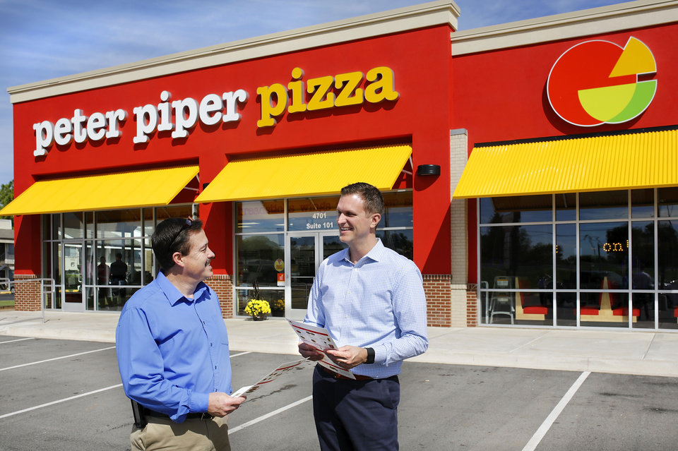 Photo -  Jason Greenwood, right, chief marketing officer for Peter Piper Pizza, talks with Michael Gaines, district manager, in front of the company's new restaurant. [Photo by Jim Beckel]