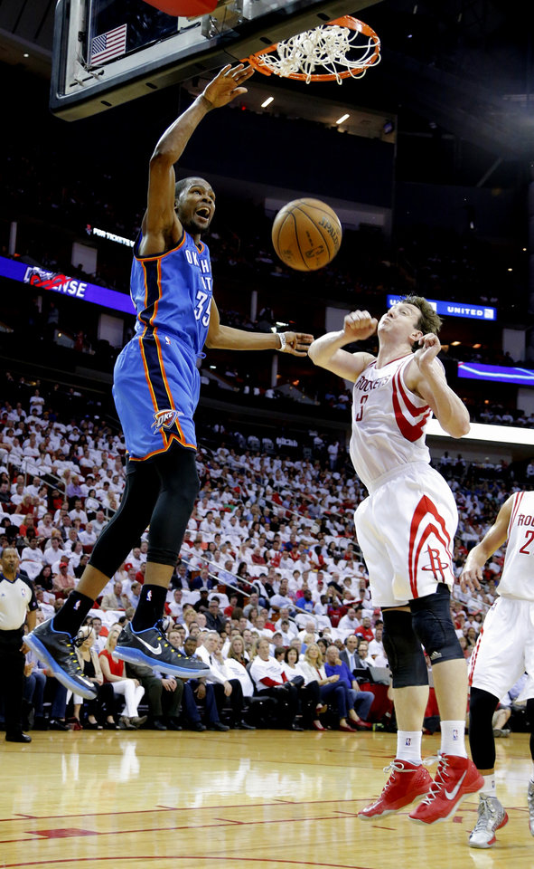 Oklahoma City\'s Kevin Durant dunks the ball beside Houston\'s Omer Asik during Game 3 in the first round of the NBA playoffs between the Oklahoma City Thunder and the Houston Rockets at the Toyota Center in Houston, Texas, Sat., April 27, 2013. Photo by Bryan Terry, The Oklahoman