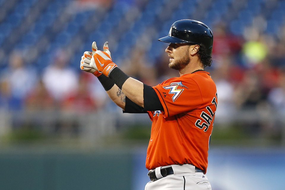 Photo - Miami Marlins' Jarrod Saltalamacchia gestures to his dugout after hitting a two-run double off Philadelphia Phillies starting pitcher A.J. Burnett during the fourth inning of a baseball game, Wednesday, June 25, 2014, in Philadelphia. (AP Photo/Matt Slocum)