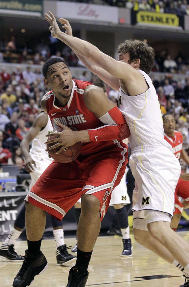 Photo -   Ohio State forward Jared Sullinger, left, drives to the basket against Michigan forward Zack Novak in the first half of an NCAA college basketball game in the semifinals of the Big Ten Conference tournament in Indianapolis, Saturday, March 10, 2012. (AP Photo/Michael Conroy)