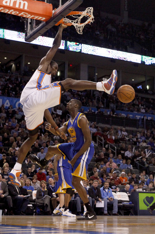 Photo - Oklahoma City's Serge Ibaka (9) dunks the ball over Golden State's Ekpe Udoh (20) during the NBA basketball game between the Oklahoma City Thunder and the Golden State Warriors at the Oklahoma City Arena, Tuesday, March 29, 2011. Photo by Bryan Terry, The Oklahoman