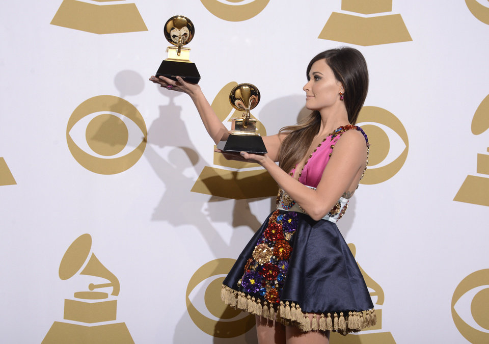 """Photo - Kacey Musgraves poses in the press room with the awards for best country album for """"Same Trailer Different Park"""" and best country song for """"Merry Go Round"""" at the 56th annual Grammy Awards at Staples Center on Sunday, Jan. 26, 2014, in Los Angeles. (Photo by Dan Steinberg/Invision/AP)"""