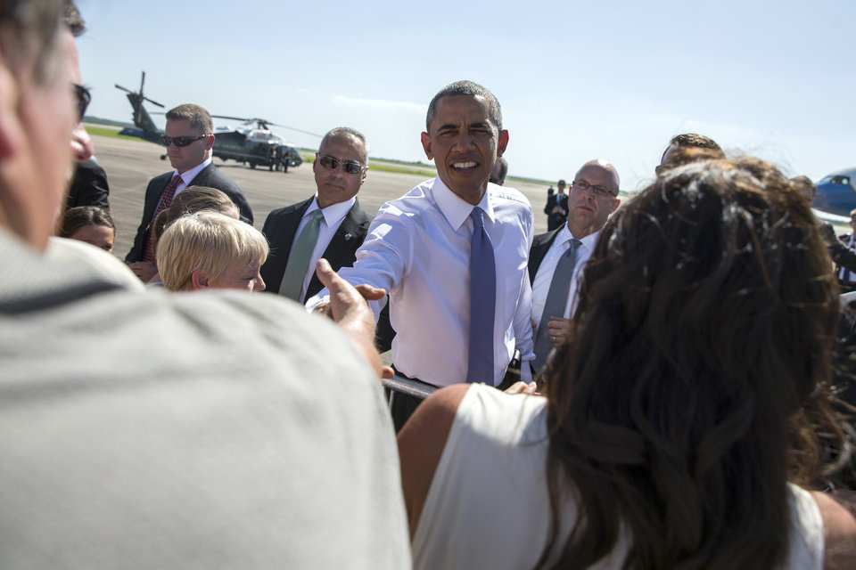 Photo - President Barack Obama shakes hands as he arrives at North Texas Regional Airport, on Wednesday, July 15, 2015, in Denison, Texas. Obama is traveling to Durant, Okla., to deliver a speech in the Choctaw Nation on economic opportunities for underprivileged communities across the nation. (AP Photo/Evan Vucci)