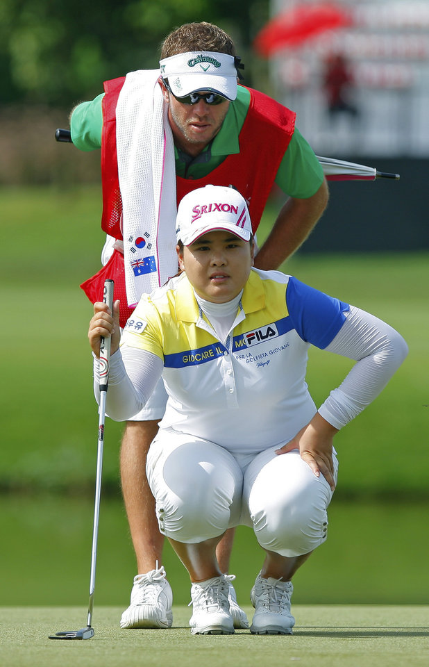 Inbee Park, foreground, of South Korea lines up her putt with her caddie on the 2nd green during the final round of the LPGA Malaysia golf tournament at Kuala Lumpur Golf and Country Club in Kuala Lumpur, Malaysia, Sunday, Oct. 14, 2012. (AP Photo/Lai Seng Sin)