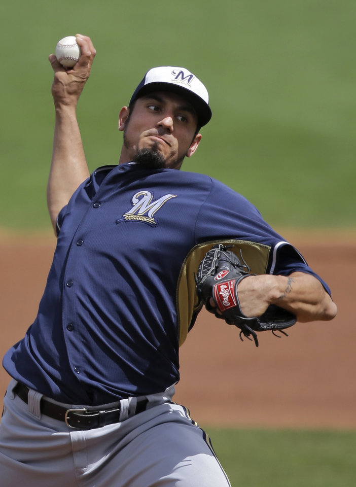 Photo - Milwaukee Brewers starting pitcher Matt Garza delivers against the Cincinnati Reds in the first inning of a spring exhibition baseball game Sunday, March 23, 2014, in Goodyear, Ariz. (AP Photo/Mark Duncan)