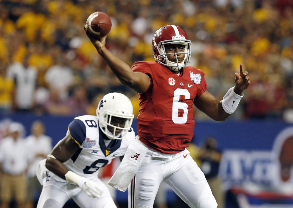 Photo - Alabama quarterback Blake Sims (6) throws under pressure from West Virginia safety Karl Joseph (8) during the first half of an NCAA college football game Saturday, Aug. 30, 2014, in Atlanta.  (AP Photo/ Brynn Anderson)
