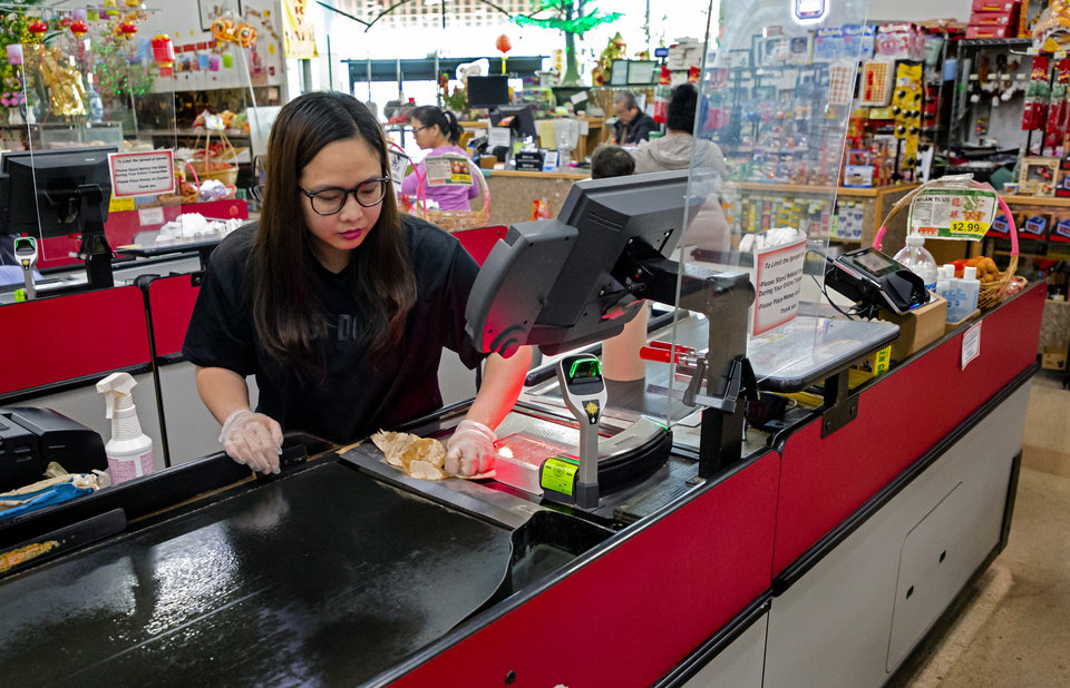 Photo - Super Cao Nguyen cashier, Ngoc Tran cleans the belt from behind the newly installed plexiglass barriers between customers and cashiers to help prevent the spread of COVID-19 at Super Cao Nguyen in Oklahoma City, Okla. on Thursday, March 26, 2020. [Chris Landsberger/The Oklahoman]