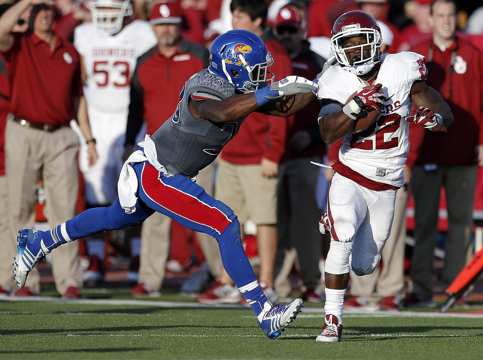 Photo - OU's Roy Finch (22) is tackled by KU's Dexter Linton (23) in the fourth quarter during of the college football game between the University of Oklahoma Sooners (OU) and the University of Kansas Jayhawks (KU) at Memorial Stadium in Lawrence, Kan., Saturday, Oct. 19, 2013. OU won 34-19. Photo by Sarah Phipps, The Oklahoman