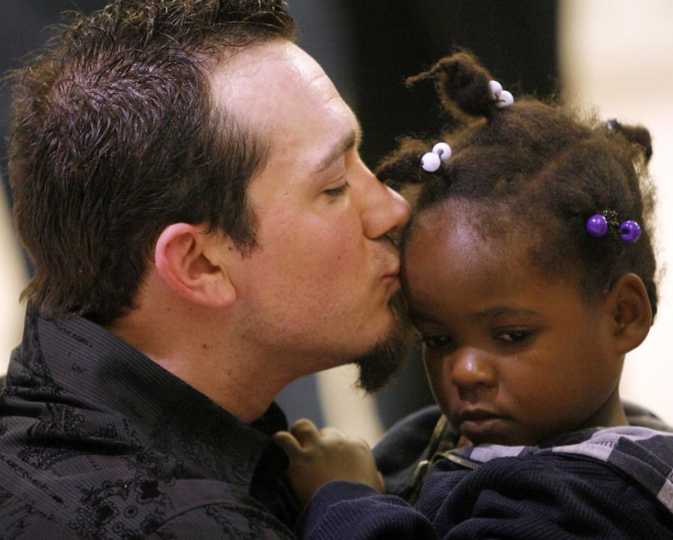 Photo -  ADOPTEES / HAITIAN ADOPTION / ADOPT / ADOPTED / CHILD / CHILDREN / KIDS / HAITI: Stephen Lee kisses his newly adopted daughter Biverlie as they meet at Will Rogers World Airport in Oklahoma City early on Thursday, Jan. 21, 2010. Photo by John Clanton, The Oklahoman ORG XMIT: KOD