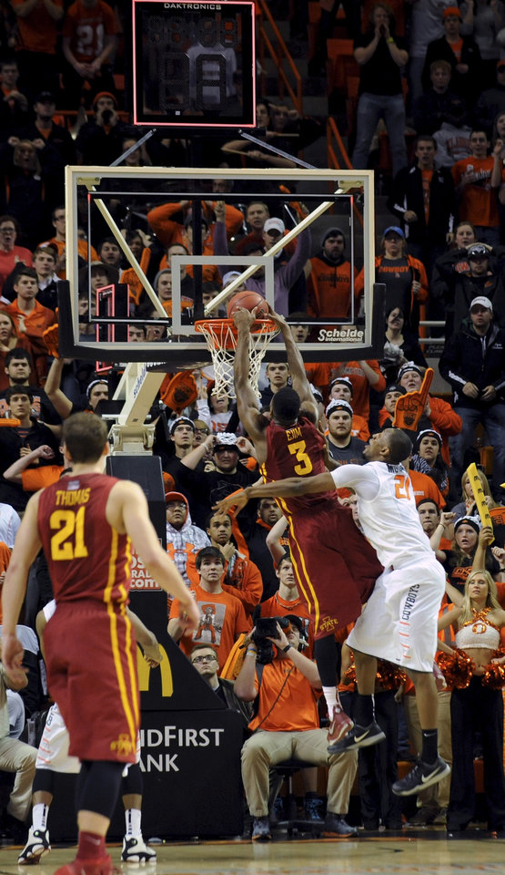 Photo - Iowa State forward Melvin Ejim, center, under pressure from Oklahoma State center Kamari Murphy, right, dunks the ball too late to avoid a 2nd overtime, during an NCAA college basketball game in Stillwater, Okla., Monday, Feb. 3, 2014. Ejim scored 22 points in the 98-97 win over Oklahoma State. (AP Photo/Brody Schmidt)