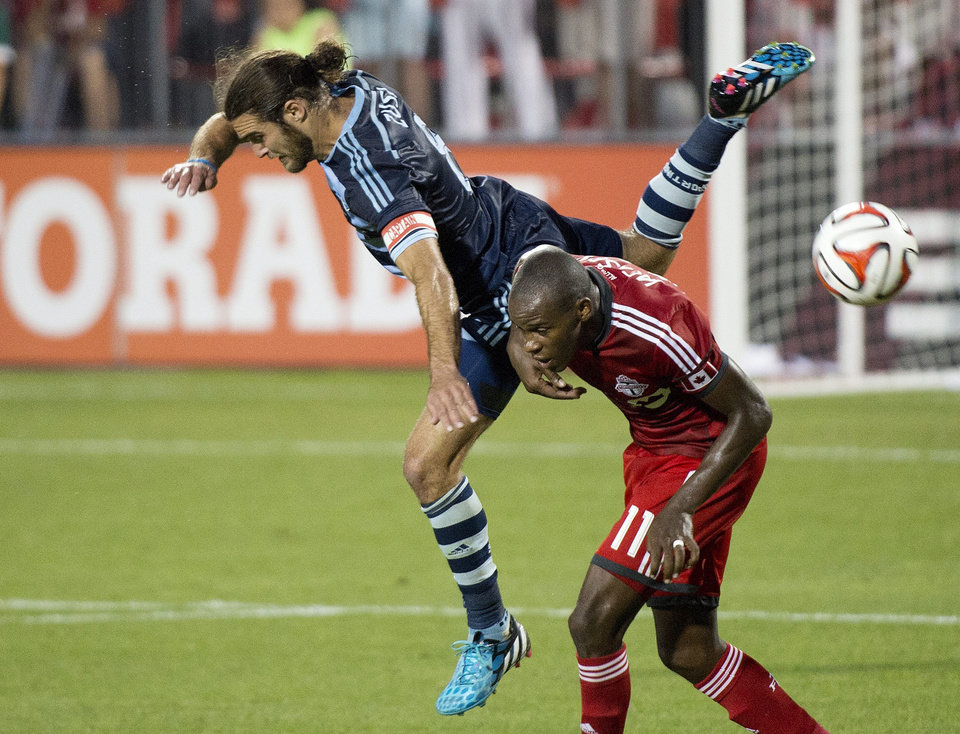 Photo - Toronto FC midfielder Jackson, right, battles for the ball against Sporting Kansas City's Graham Zusi, left, during second-half MLS soccer action in Toronto, Saturday, July 26, 2014. (AP Photo/The Canadian Press, Nathan Denette)