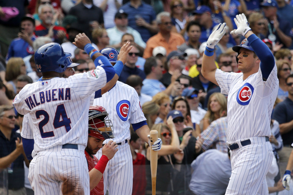 Photo - Chicago Cubs' Ryan Sweeney, right, celebrates his three-run home run off St. Louis Cardinals starting pitcher Joe Kelly with Luis Valbuena (24) during the second inning of a baseball game Friday, July 25, 2014, in Chicago. Valbuena and Welington Castillo also scored on the play. (AP Photo/Charles Rex Arbogast)