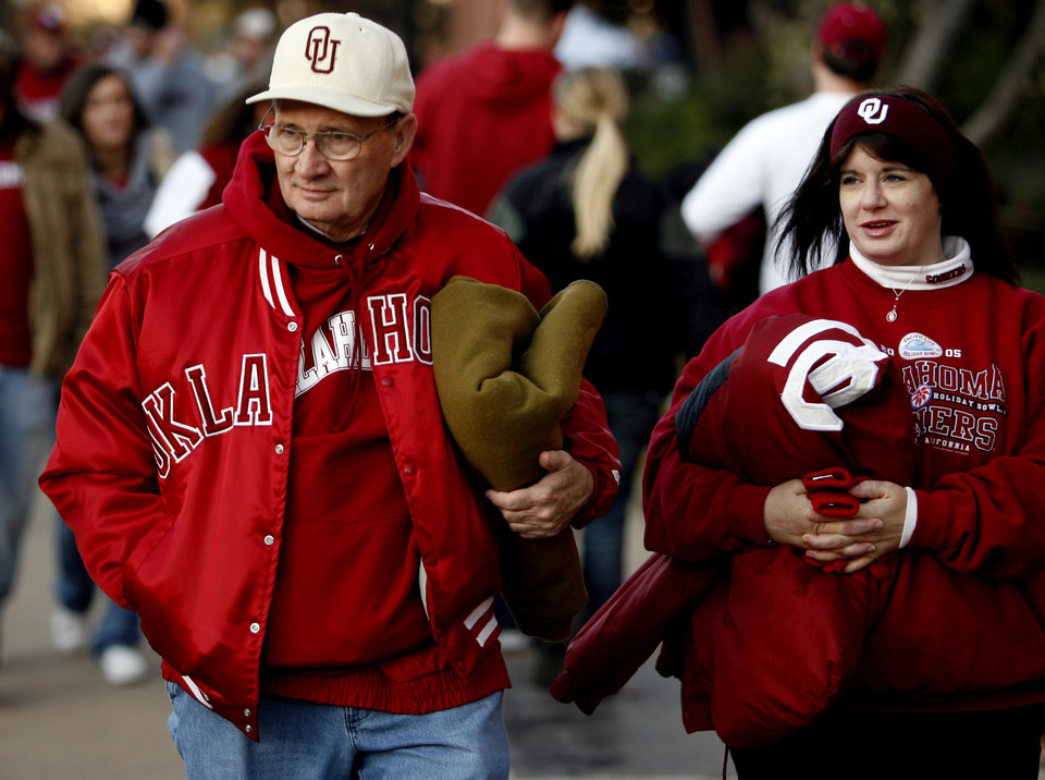 Photo - Charlie Northcut and his daughter Beth Manning of Sand Springs are warmly dressed as they make their way to the college football game between the University of Oklahoma Sooners and Texas Tech University at the Gaylord Family -- Oklahoma Memorial Stadium on Saturday, Nov. 22, 2008, in Norman, Okla.   BY STEVE SISNEY, THE OKLAHOMAN