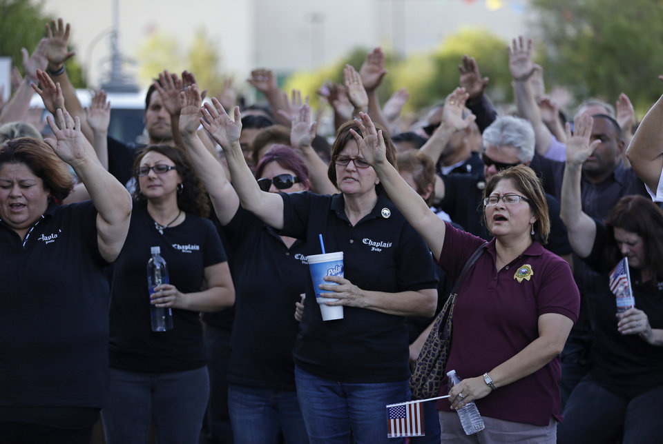 Photo - People pray during a vigil at CiCi's Pizza Monday, June 9, 2014 in Las Vegas. The vigil was held to honor two Las Vegas Metropolitan Police officers and a bystander who were killed Sunday. (AP Photo/John Locher)