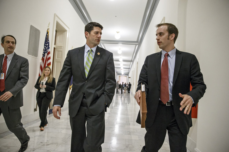 Photo - House Budget Committee Chairman Rep. Paul Ryan, R-Wis., center, confers with aide Conor Sweeney as he leaves a closed-door meeting on Capitol Hill in Washington, Wednesday, April 2, 2014, before a markup session where House Republicans will craft a slashing plan to try to balance the budget within 10 years. (AP Photo/J. Scott Applewhite)