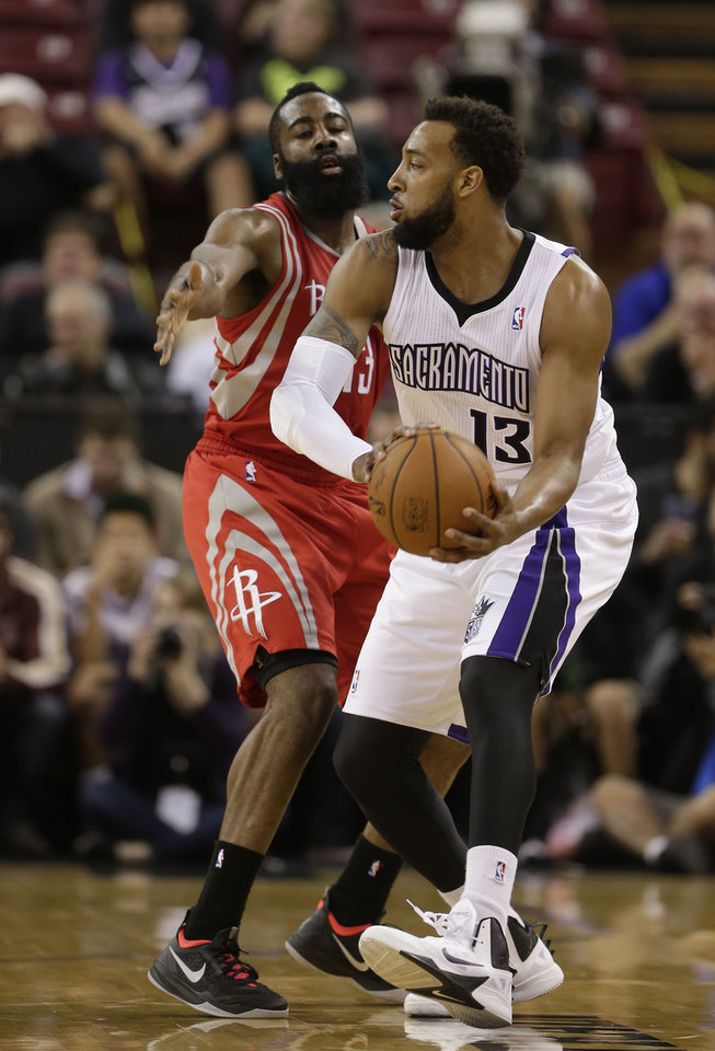 Photo - Sacramento Kings forward Derrick Williams, (13) tries to pass off against Houston Rockets guard James Harden during the first quarter of an NBA basketball game in Sacramento, Calif., Tuesday Feb. 25, 2014.(AP Photo/Rich Pedroncelli)