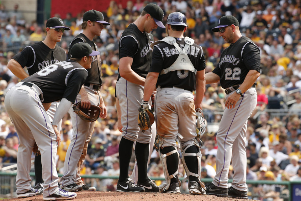 Photo - Colorado Rockies manager Walt Weiss (22) takes the ball from relief pitcher Matt Belisle, center, during the seventh inning of a baseball game against the Pittsburgh Pirates in Pittsburgh Sunday, July 20, 2014. The Pirates won 5-3. (AP Photo/Gene J. Puskar)