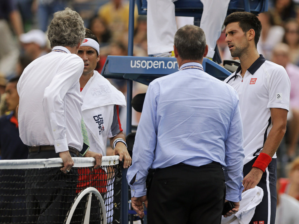 Photo -   Spain's David Ferrer, second from left, and Serbia's Novak Djokovic, far right, talk with officials during a semifinal match at the 2012 US Open tennis tournament, Saturday, Sept. 8, 2012, in New York. The match was suspended in the first set because of approaching inclement weather. (AP Photo/Mike Groll)