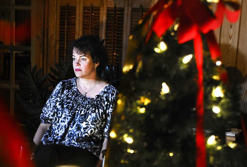 Photo - In this Monday, Jan. 14, 2013 photo, Veronique Pozner sits next to a decorated tree, picked out by her son Noah, at a friend's house during an interview with The Associated Press in Danbury, Conn.  Pozner's son Noah was a victim of the Sandy Hook Elementary School shooting in Newtown, Conn.  Her family has submitted a detailed proposal to a White House task force that proposes a range of reforms, including federal grants for public schools to undergo reviews to improve security and requiring gun owners to lock up their weapons in their homes if the guns could be accessed by mentally ill or dangerous people. (AP Photo/Jessica Hill)