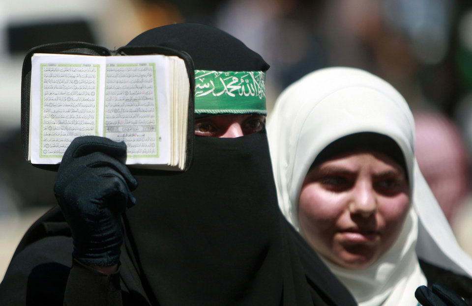 Photo - A Palestinian supporter of Hamas holds the Quran as others shout slogans against the Israeli military action in Gaza, during a demonstration in the West Bank town of Tulkarem town on Friday, Aug. 1, 2014. A Palestinian man was shot and killed during clashes with Israeli troops, following the demonstration in Tulkarem, Palestinian security sources said. (AP Photo/Mohammed Ballas)
