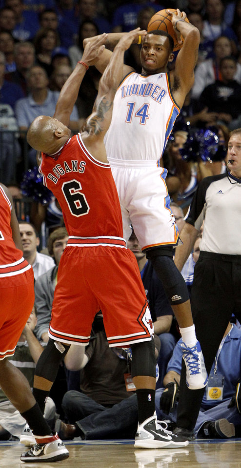 Photo - Oklahoma City's Daequan Cook passes the ball over Chicago's Keith Bogans during the NBA basketball game between the Oklahoma City Thunder and the Chicago Bulls in the Oklahoma City Arena on Wednesday, Oct. 27, 2010. Photo by Bryan Terry, The Oklahoman