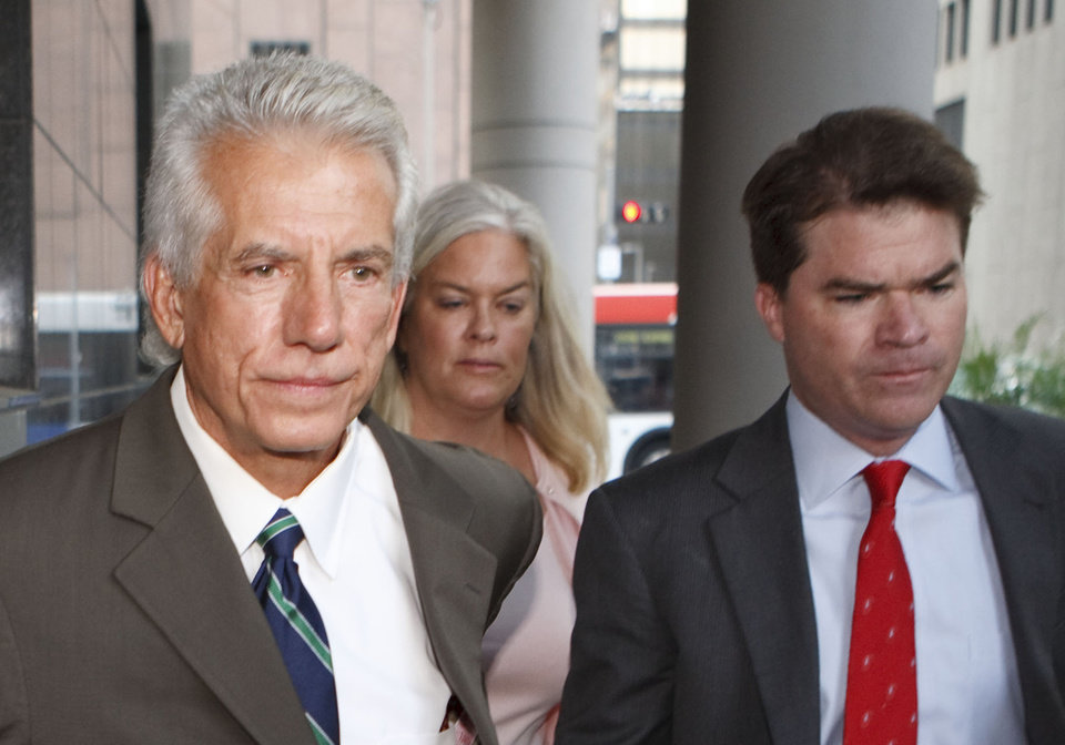 FILE - In this Aug. 27, 2009 file photo former Stanford Financial CFO James M. Davis, left, arrives at federal court in Houston with his wife and his attorney David Finn, right. Davis, the star prosecution witness in the trial of convicted Texas financier R. Allen Stanford, was sentenced Tuesday, Jan. 22, 2013 to five years in prison for helping to bilk investors out of more than $7 billion in one of the biggest Ponzi schemes in U.S. history. (AP Photo/Michael Stravato, File)