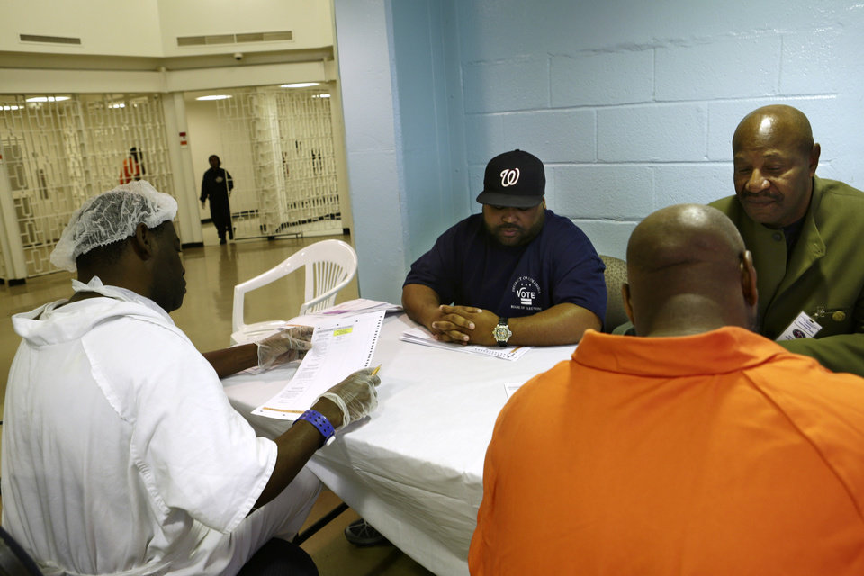 Photo -   In this photo taken Oct. 24, 2012, Arlin Budoo, center, and Tyrone Parker, right, help prisoners to vote at the D.C. Jail in Washington. The voters at this southeast Washington polling place were all dressed alike: orange jumpsuit, white shoes. And when they finished voting they went back to their cell block, not back to work. Still, voting inside the D.C. Jail looked a lot like voting at precincts around the country.(AP Photo/Jacquelyn Martin)