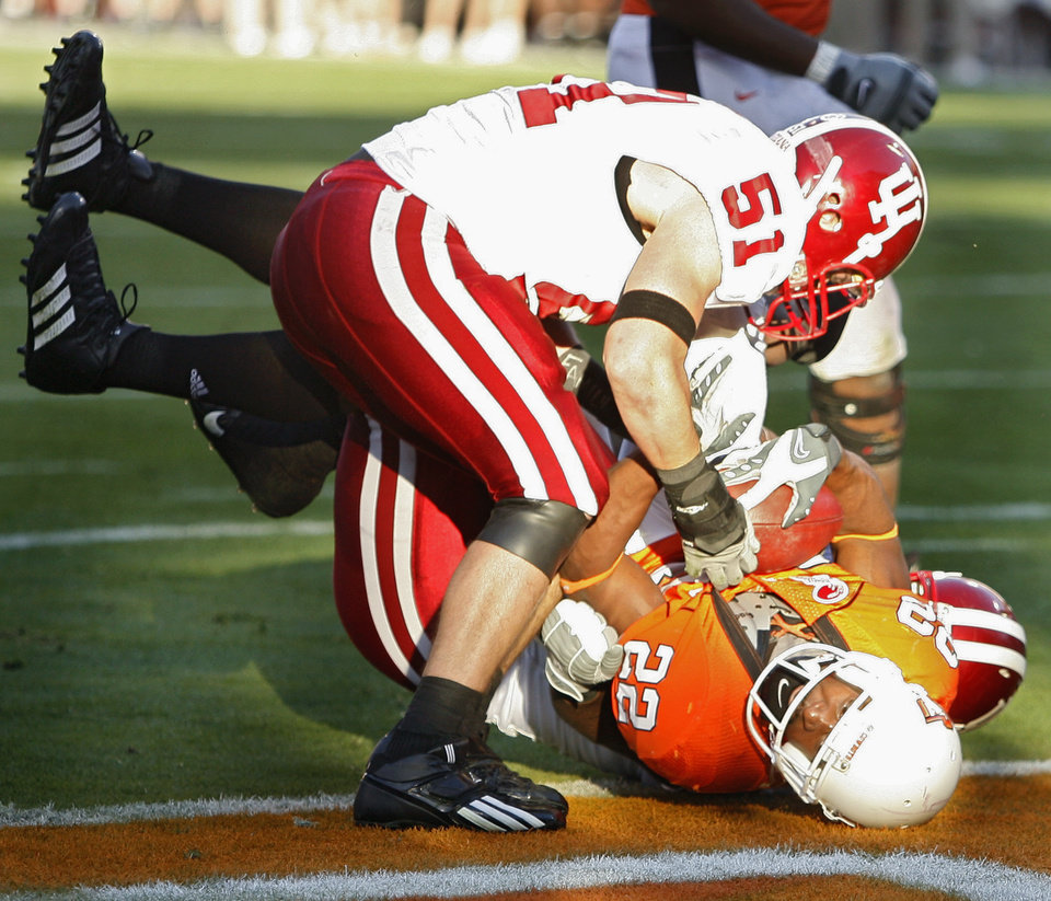 Oklahoma State's Dantrell Savage (22) is brought down by Indiana's Adam McClurg (51) in the first half during the Insight Bowl college football game between Oklahoma State University (OSU) and the Indiana University Hoosiers (IU) at Sun Devil Stadium on Monday, Dec. 31, 2007, in Tempe, Ariz. 