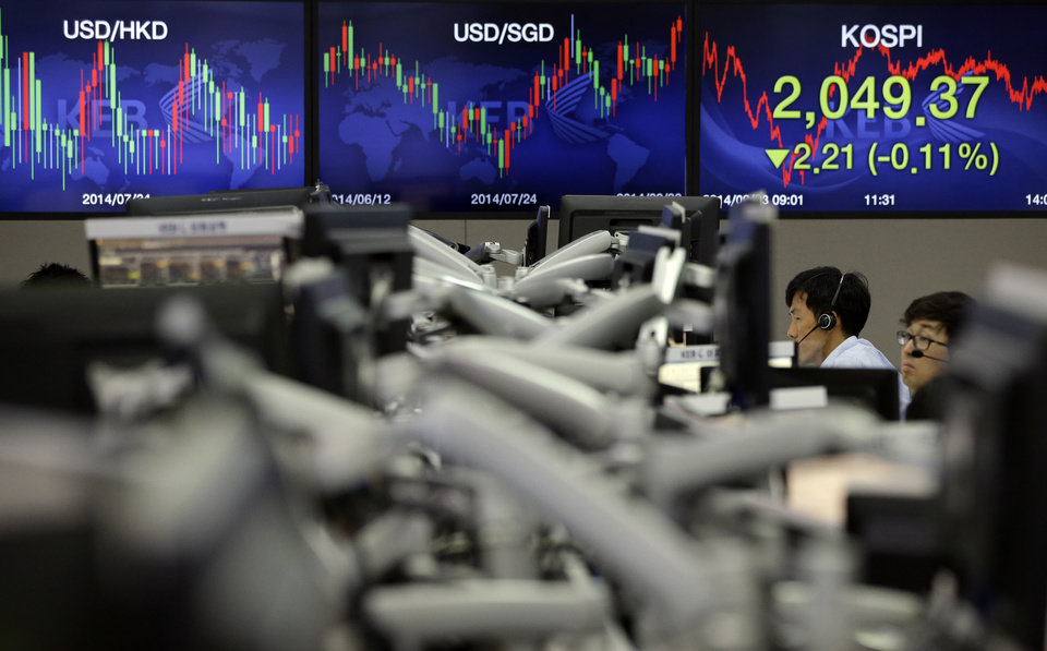 Photo - Currency traders work near a screen showing the Korea Composite Stock Price Index (KOSPI), right, at the foreign exchange dealing room of the Korea Exchange Bank headquarters in Seoul, South Korea, Wednesday, Sept. 3, 2014. Asian stock markets rose Wednesday, lifted by new signs of strength in the U.S. economy and expectations that Europe's central bank will provide more support to the flagging region. (AP Photo/Lee Jin-man)