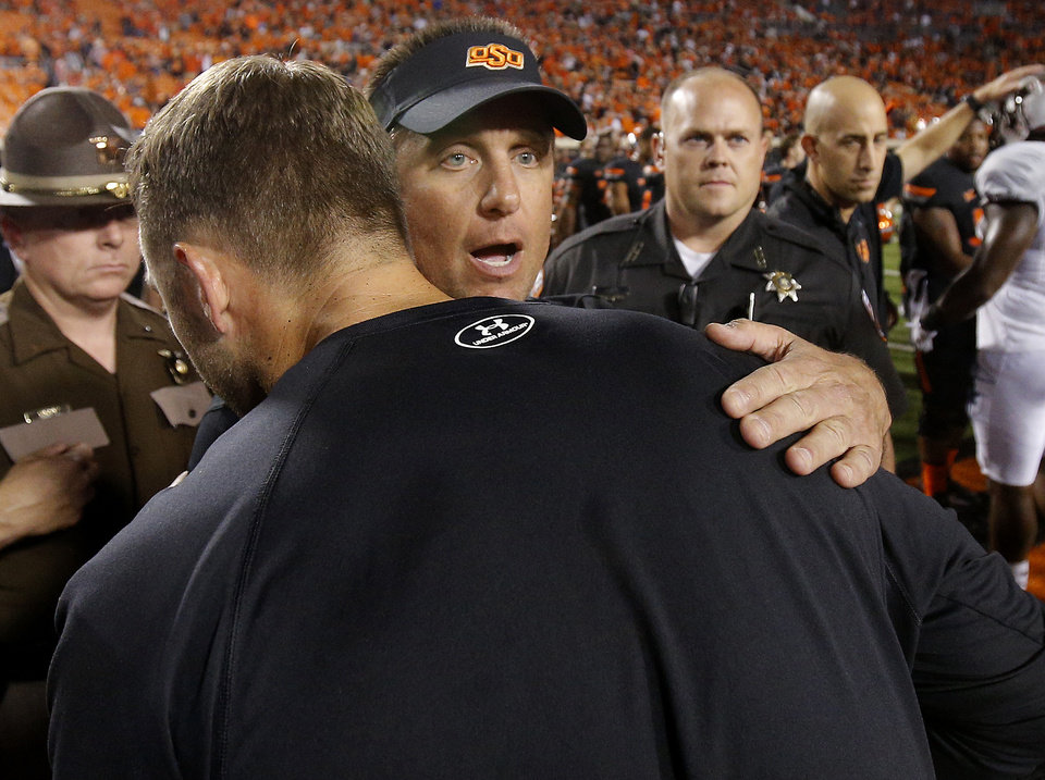 Photo - Oklahoma State coach Mike Gundy meets with Texas Tech coach Kliff Kingsbury after a college football game between the Oklahoma State Cowboys (OSU) and the Texas Tech Red Raiders at Boone Pickens Stadium in Stillwater, Okla., Thursday, Sept. 25, 2014. Photo by Bryan Terry, The Oklahoman