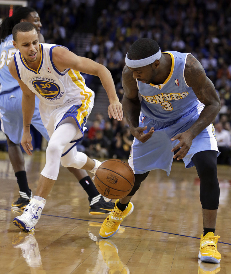 Photo - Denver Nuggets' Ty Lawson, right, and Golden State Warriors' Stephen Curry chase a loose ball during the first half of an NBA basketball game Wednesday, Jan. 15, 2014, in Oakland, Calif. (AP Photo/Ben Margot)