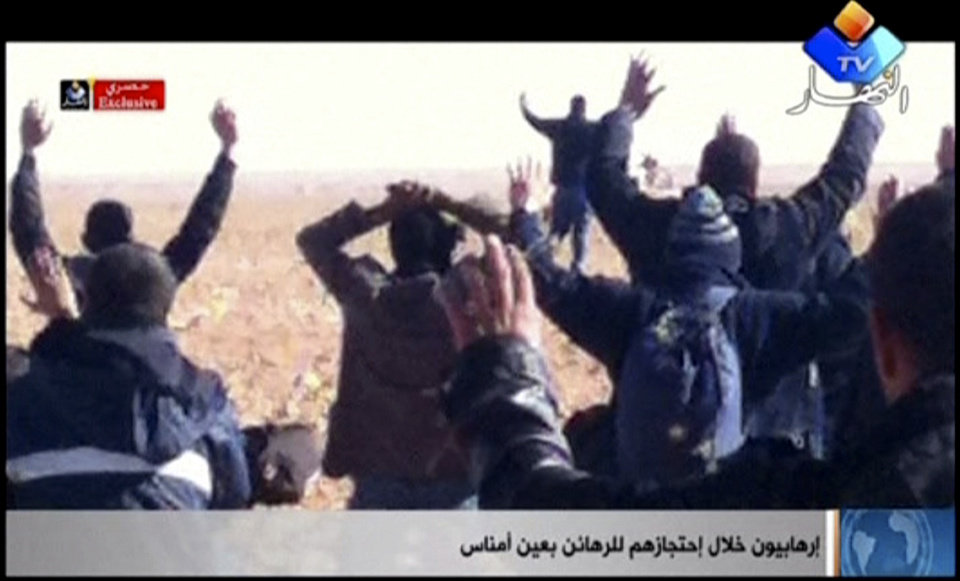 Photo - In this image made from video, a group of people believed to be hostages kneel in the sand with their hands in the air at an unknown location in Algeria. An Algerian security official says de-mining squads searching for explosives found