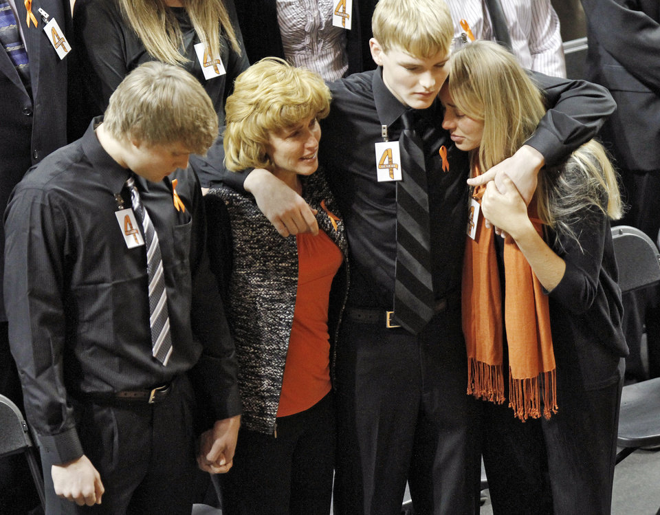 Photo - Alex Budke, left, stands next to his mother Shelley, brother Brett and daughter Sara during the memorial service for Oklahoma State head basketball coach Kurt Budke and assistant coach Miranda Serna at Gallagher-Iba Arena on Monday, Nov. 21, 2011 in Stillwater, Okla. The two were killed in a plane crash along with former state senator Olin Branstetter and his wife Paula while on a recruiting trip in central Arkansas last Thursday. Photo by Chris Landsberger, The Oklahoman