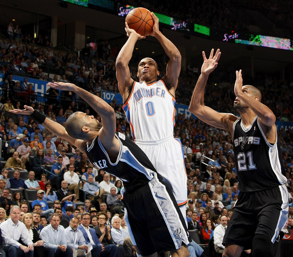 Oklahoma City's Russell Westbrook (0) takes a shot between San Antonio's Tony Parker (9) and Tim Duncan (21) during the NBA basketball game between the Oklahoma City Thunder and the San Antonio Spurs at Chesapeake Energy Arena in Oklahoma City, Friday, March 16, 2012. Photo by Nate Billings, The Oklahoman