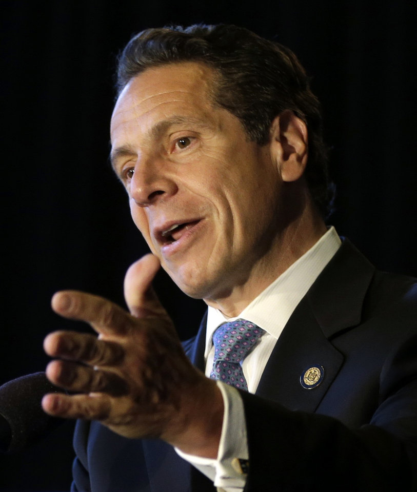 Photo - New York Governor Andrew Cuomo speaks during a ceremonial bill signing in New York, Monday, July 7, 2014. New York has become the 23rd state in the U.S. to authorize medical marijuana,  though the state's program is one of the nation's most restrictive.  Cuomo signed the measure into law on Saturday and held the formal signing ceremony on Monday to highlight the new law.  When the program gets up and running in about 18 months, patients with diseases including AIDS, cancer and epilepsy will be able to obtain non-smokeable versions of the drug. Instead, the drug must be ingested or administered through a vaporizer or oil base.  (AP Photo/Seth Wenig)
