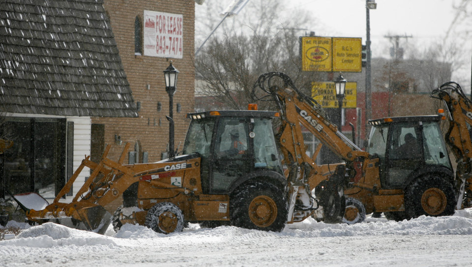 Photo - Front end loader clears snow from downtown Edmond, Okla., on Wednesday, Feb. 9, 2011.  Photo by Bryan Terry, The Oklahoman