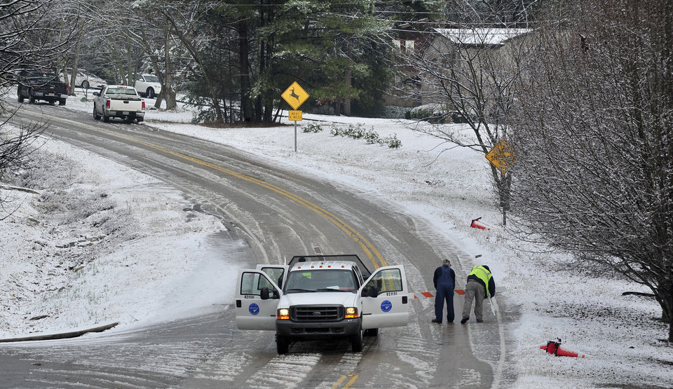 Photo - City of Huntsville workers  set up road blocks on Green Mountain Road while a salt truck clears the road during a brief winter storm which brought light snow and icy roads to north Alabama Thursday, Jan. 17, 2013 in Huntsville, Ala. A winter storm made its way across the Southeast on Thursday, dumping snow in states recovering from days of rain, playing a role in at least one fatality, and leaving thousands without power. (AP Photo/AL.com, Eric Schultz)