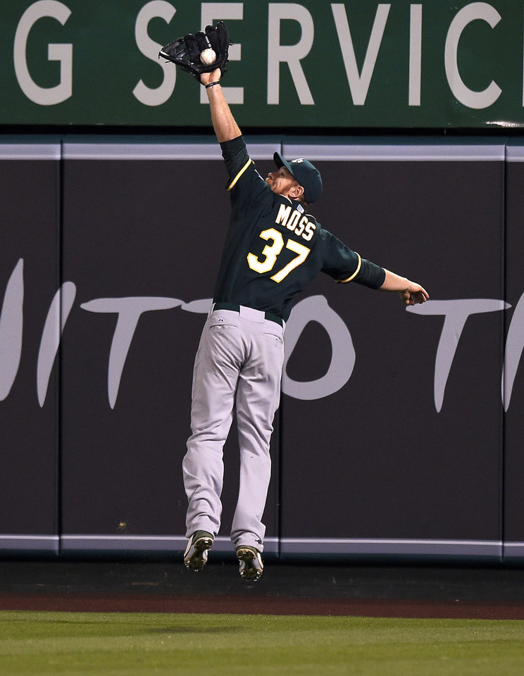 Photo - Oakland Athletics first baseman Brandon Moss makes a catch on a fly ball hit by Los Angeles Angels' Howie Kendrick during the seventh inning of a baseball game, Wednesday, April 16, 2014, in Anaheim, Calif. (AP Photo/Mark J. Terrill)