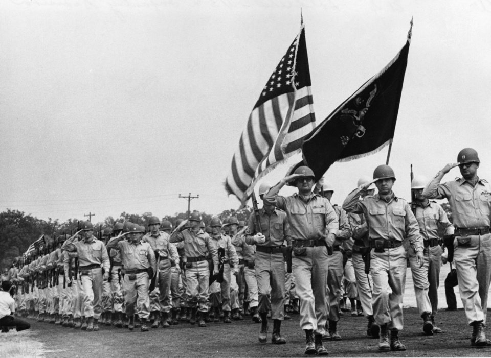 Photo - Passing the review at Fort Chaffee, Ark., Saturday before about 1,500 Oklahomans were members of the 45th Infantry Division.  The 6,000 Thunderbirds have completed the first of two weeks of summer training.  In the reviewing stand was Gov. Bellmon, standing beside Maj. Gen. Daugherty, division commander.  An 83-degree breeze kept marchers comfortable.   Staff photo by George Tapscott.  Photo dated 08/08/1964 and published on 08/09/1964 in The Daily Oklahoman.