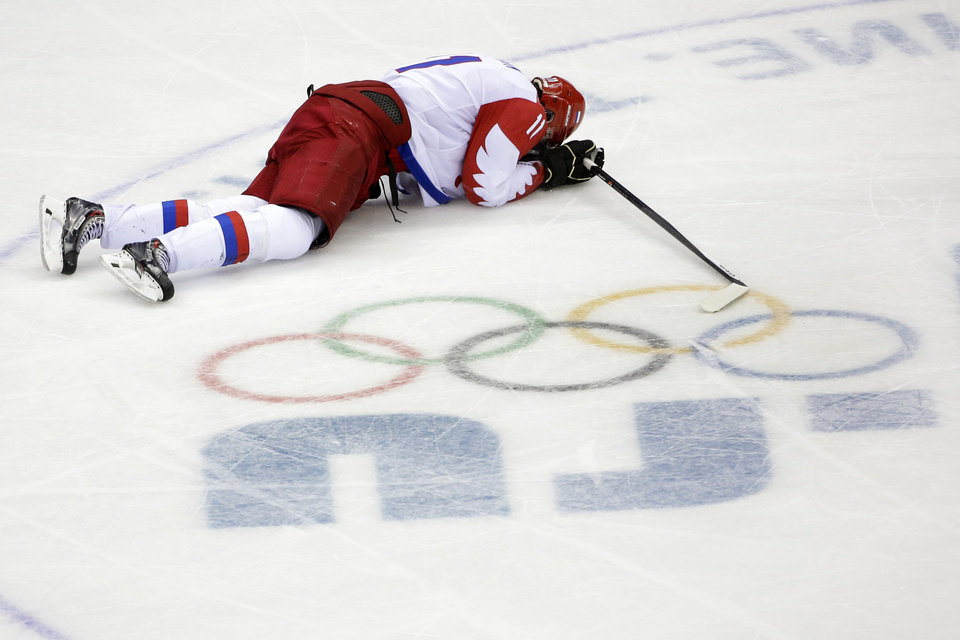 Photo - Russia forward Yevgeni Malkin lies on the ice in the closing minutes of the third period in men's quarterfinal hockey game against Finland at Bolshoy Arena at the 2014 Winter Olympics, Wednesday, Feb. 19, 2014, in Sochi, Russia. Finland defeated Russia 3-1. (AP Photo/David J. Phillip )