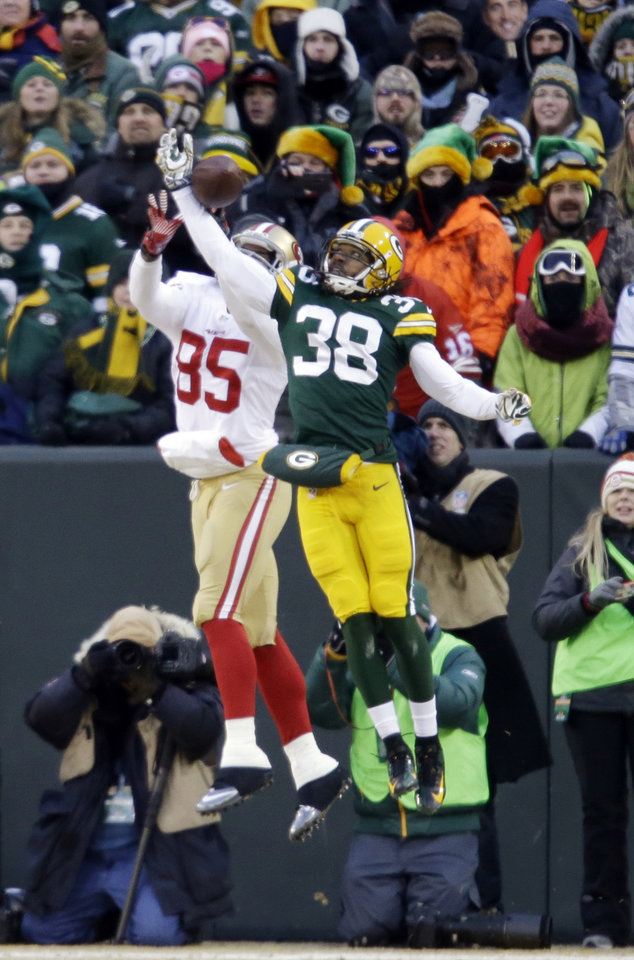 Photo - Green Bay Packers cornerback Tramon Williams (38) breaks up a pass intended for San Francisco 49ers tight end Vernon Davis (85) during the first half of an NFL wild-card playoff football game, Sunday, Jan. 5, 2014, in Green Bay, Wis. (AP Photo/Jeffrey Phelps)