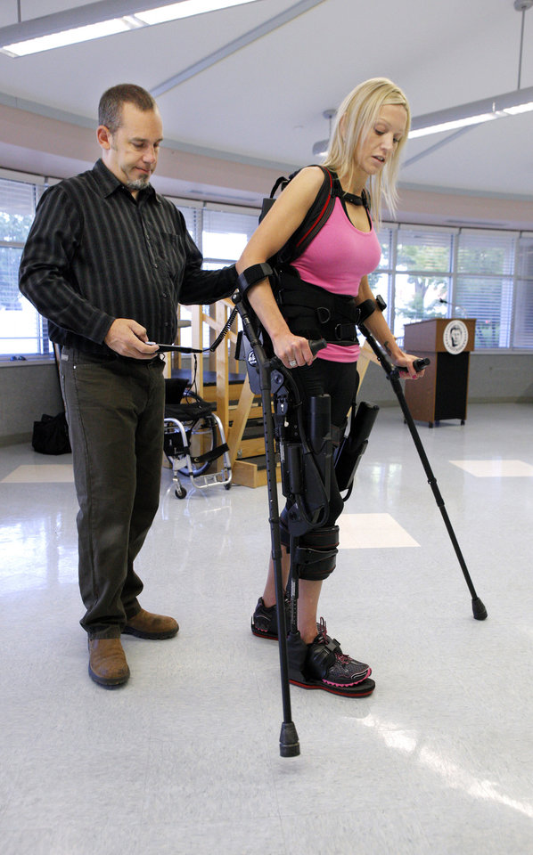 Tom Griffith, field service engineer with Ekso Bionics, helps Sarah Anderson, from San Francisco Bay Area , Calif.,  walk with the aid of the Ekso bionic suit at  Jim Thorpe Rehabilitation Integris Southwest Medical Center in Oklahoma City Wednesday, July 25, 2012. Anderson was paralyzed from the chest down after being struck by a drunk driver. Photo by Paul B. Southerland, The Oklahoman
