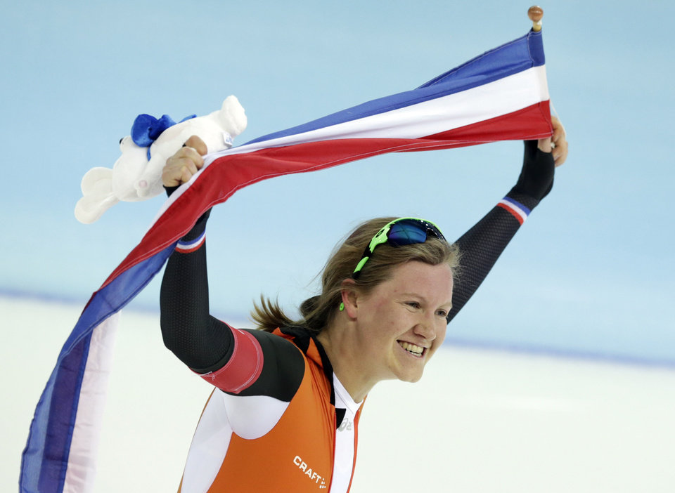 Photo - Bronze medallist Lotte van Beek of the Netherlands holds her national flag and celebrates after the women's 1,500-meter race at the Adler Arena Skating Center during the 2014 Winter Olympics in Sochi, Russia, Sunday, Feb. 16, 2014. (AP Photo/Matt Dunham)