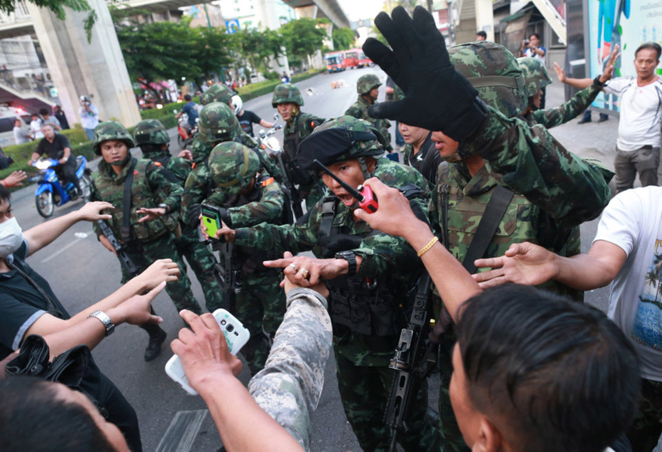 Photo - Thai soldiers scuffle with protesters during an anti-coup demonstration at the Victory Monument in Bangkok, Thailand, Saturday, May 24, 2014. Thailand's coup leaders said Saturday that they would keep former Prime Minister Yingluck Shinawatra, Cabinet members and anti-government protest leaders detained for up to a week to give them