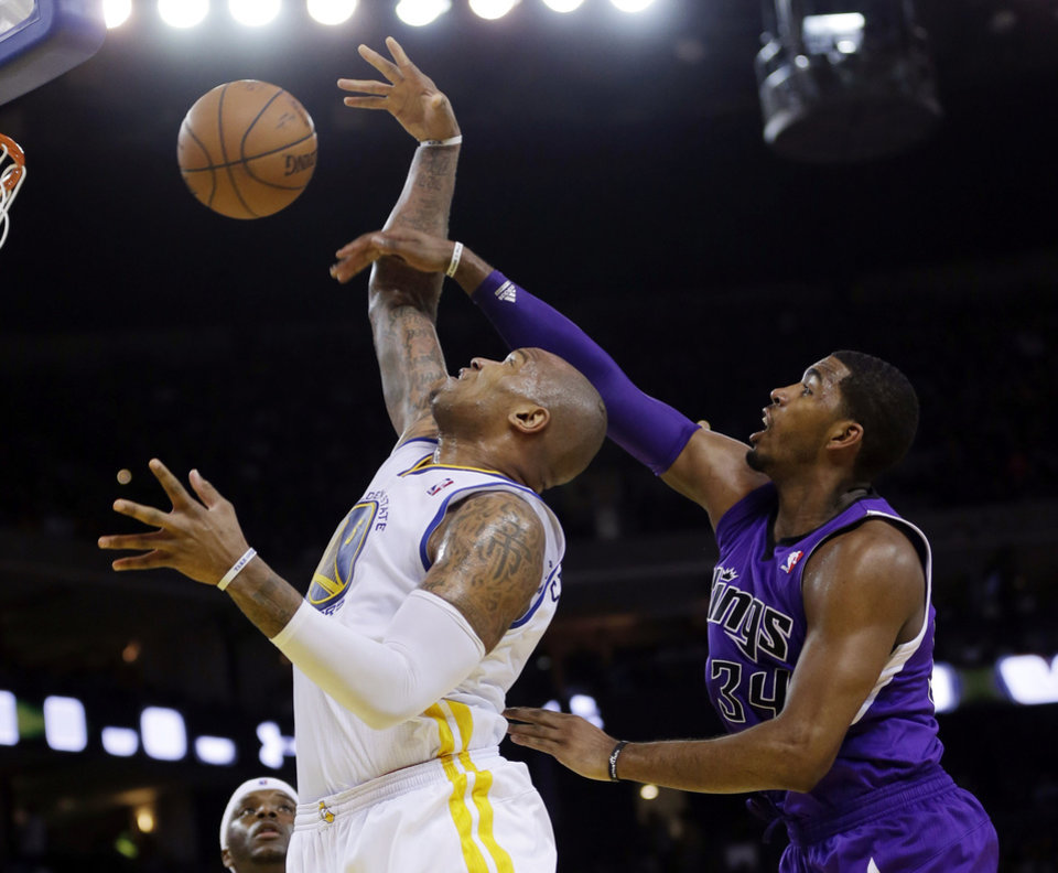 Photo - Golden State Warriors forward Marreese Speights, left, vies for a rebound next to Sacramento Kings forward Jason Thompson during the first half of an NBA basketball game Friday, April 4, 2014, in Oakland, Calif. (AP Photo/Marcio Jose Sanchez)