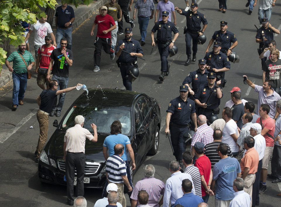 Photo - Police move in as demonstrators try to block the way while another pours water on a car, suspected to be a private taxi during a 24 hour taxi strike and protest in Madrid, Spain, Wednesday, June 11, 2014. The taxi drivers were protesting against unregulated competition from private companies, in particular, Uber, an international company that puts people in contact with each other to share cars or pay for short journeys in private vehicles within the city. (AP Photo/Paul White)