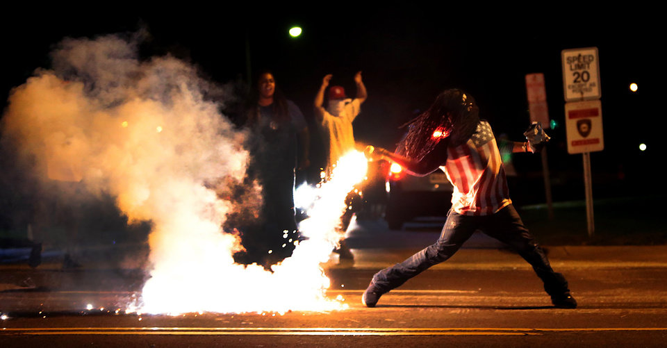 Photo - A demonstrator throws back a tear gas container after tactical officers trying to break up a group of bystanders Wednesday, Aug. 13, 2014 in West Florissant, Mo. Ferguson has been the site of nightly protests and unrest since 18-year-old Michael Brown was killed during a confrontation with an officer on Saturday. (AP Photo/St. Louis Post-Dispatch, Robert Cohen)