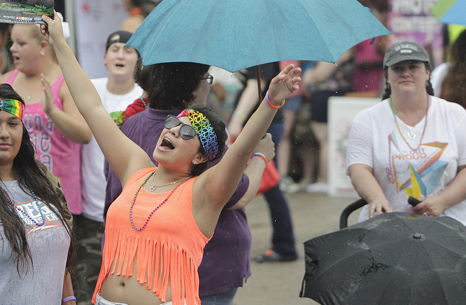 Photo - People listen to music while it rains during the Houston Pride Festival on Saturday, June 28, 2014, in Houston. (AP Photo/Houston Chronicle, Mayra Beltran)